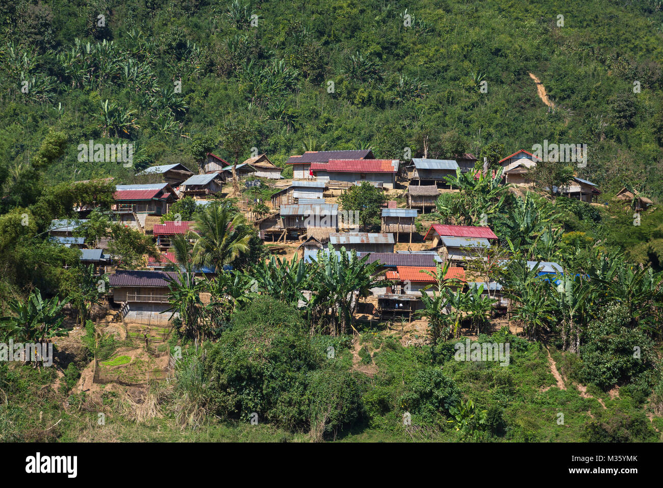 Traditional lao village landscape seen from the Mekong river in Laos - Stock Image