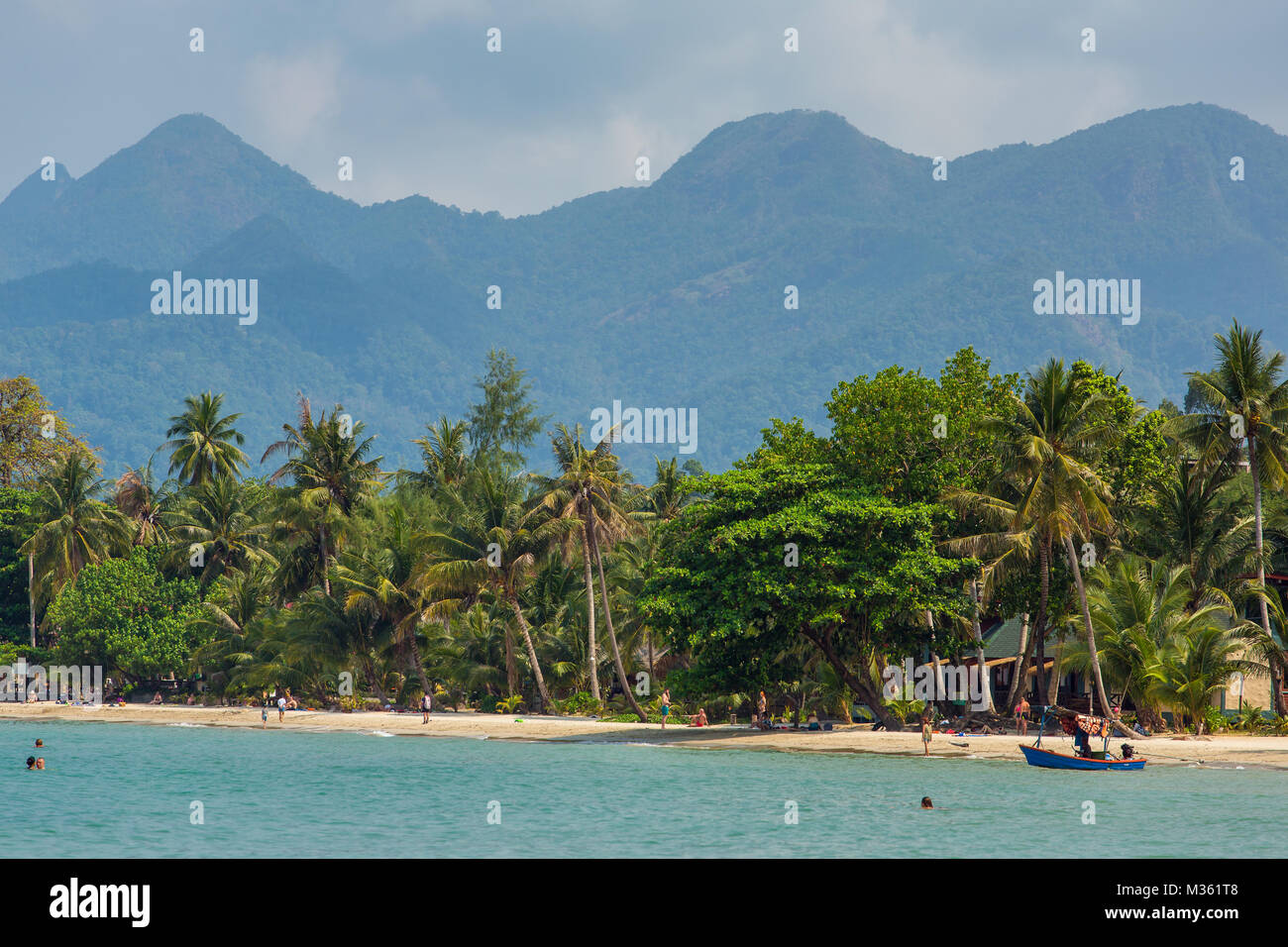 Koh Chang, Thailand - March 12, 2017: Tourists rest on the beautiful tropical beach on Koh Chang island in Thailand - Stock Image