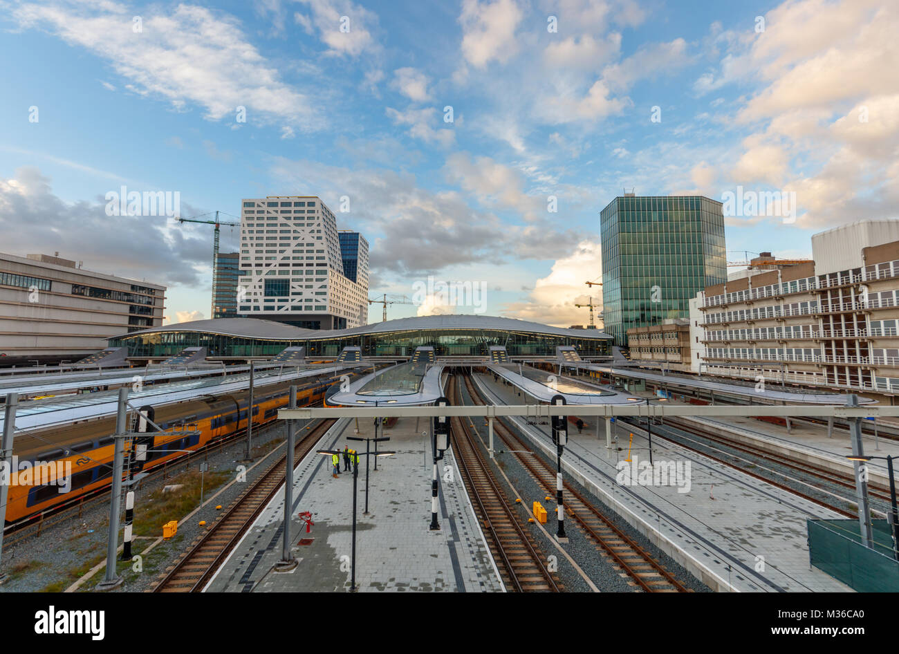 The City Hall and Utrecht Centraal railway station with platforms, trains and railways during sunset. Utrecht, The - Stock Image