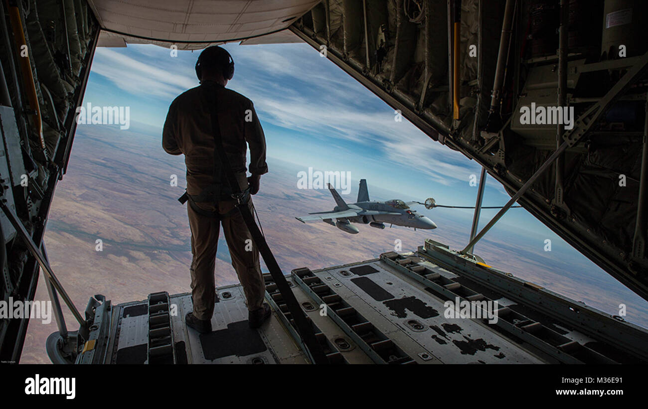U.S. Marine Corps Cpl. Chris Lawler, a crewmaster with Marine Aerial Refueler Transport Squadron (VMGR) 152, observes - Stock Image