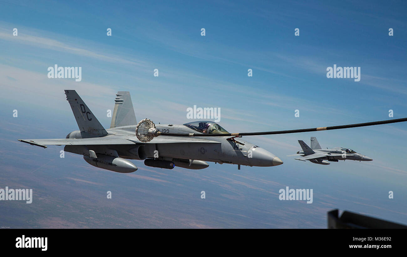 An F/A-18C Hornet with Marine Fighter Attack Squadron (VMFA) 122 moves in to catch the basket during an aerial refueling - Stock Image