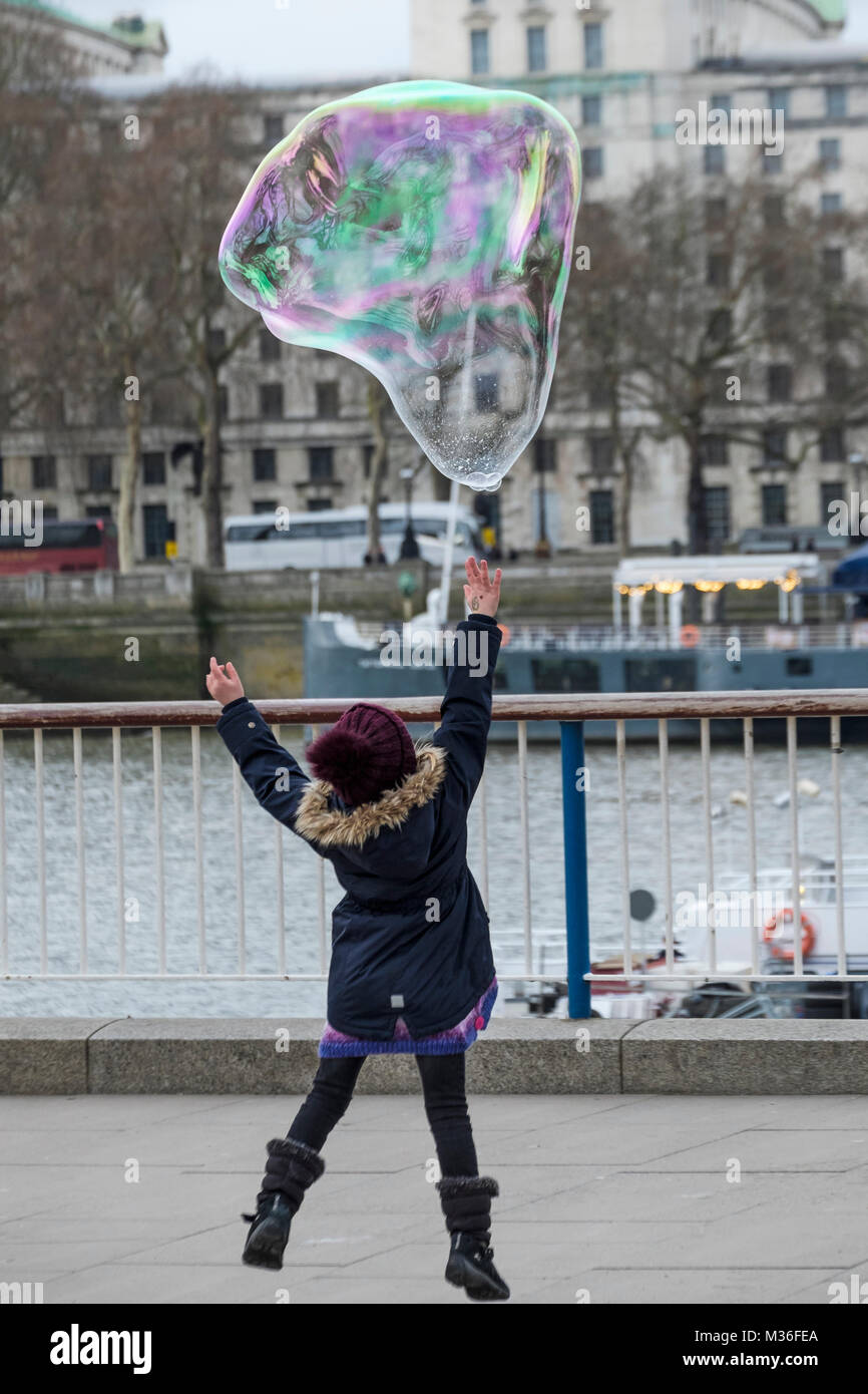 Young girl jumping to reach giant bubble, Southbank, London, UK - Stock Image