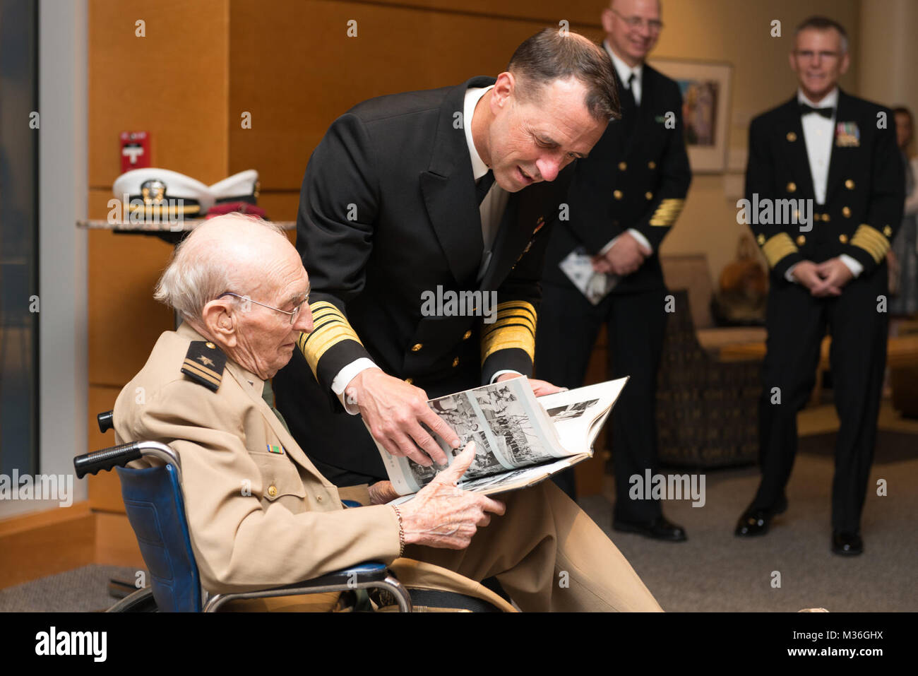 161005-N-DD694-444 BETHESDA, Md. (Oct. 5, 2016) Chief of Naval Operations Admiral John Richardson presents a cruise book to World War II veteran Norton Hurd after the Navy Birthday Concert.  The Navy Band was celebrating the Navy's 241st birthday. (U.S. Navy photo by PO1 Jonathan Barnes/Released) 161005-N-DD694-444 by United States Navy Band Stock Photo