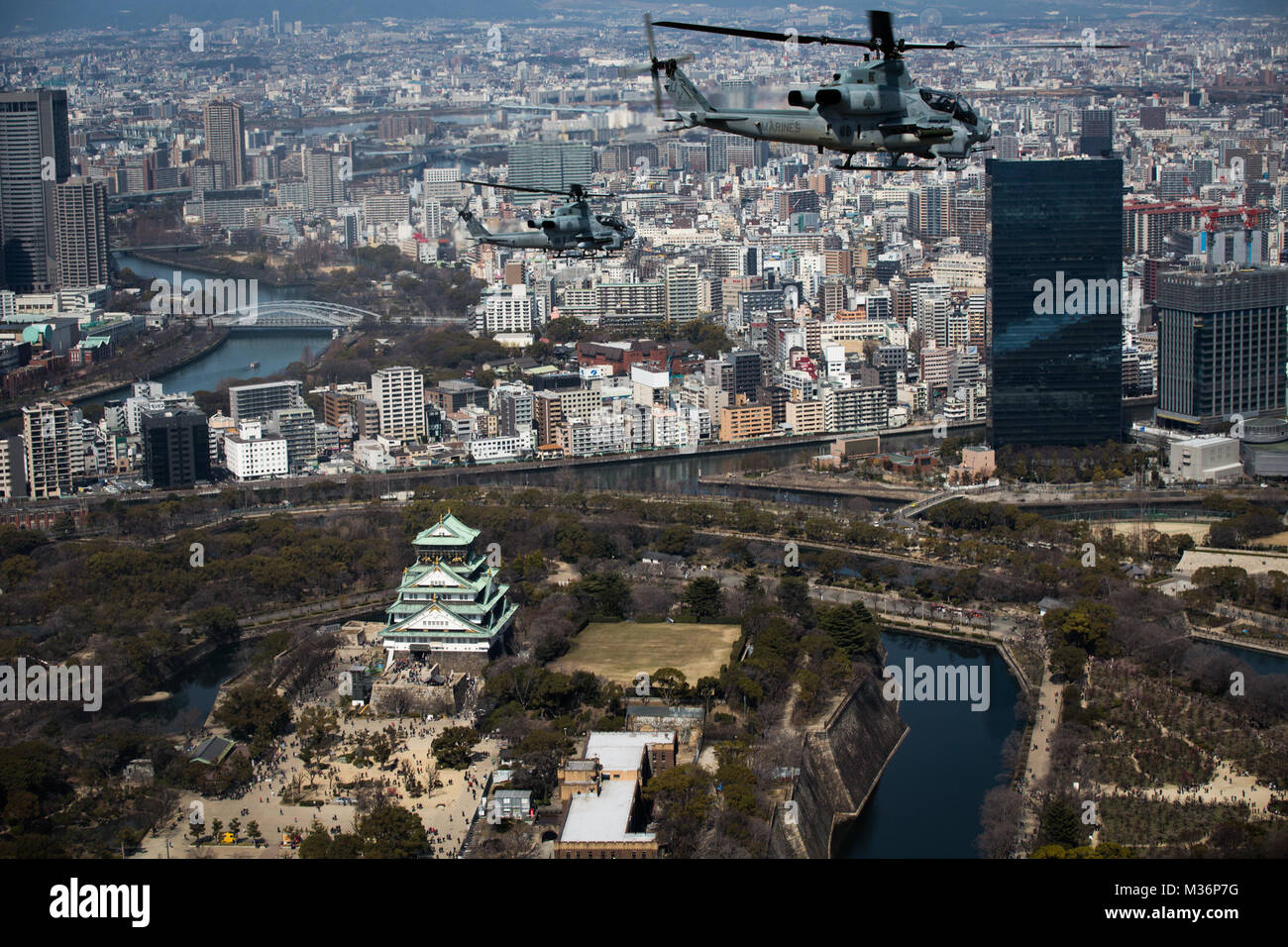 AH-1Z Vipers soar through the skies over Osaka Castle, Osaka, Japan, March 12, 2017. Marine Light Attack Helicopter Stock Photo