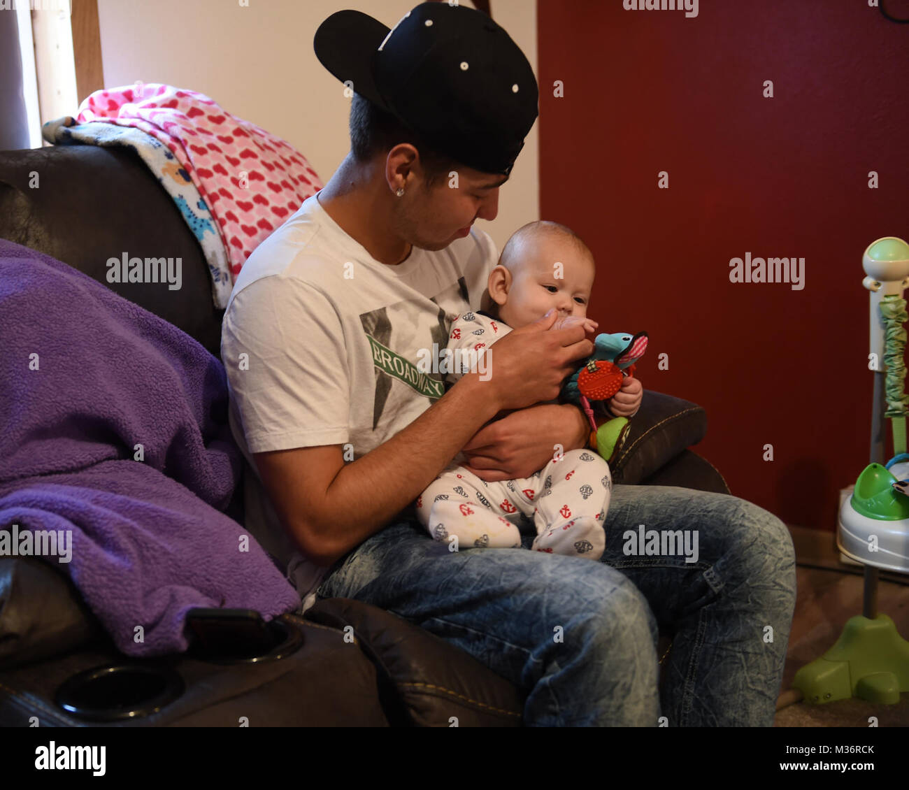 Tyger Rodriguez, 17, of Torrington, Wyoming, holds his six-month-old son Kyson, during his home visit from Wyoming - Stock Image