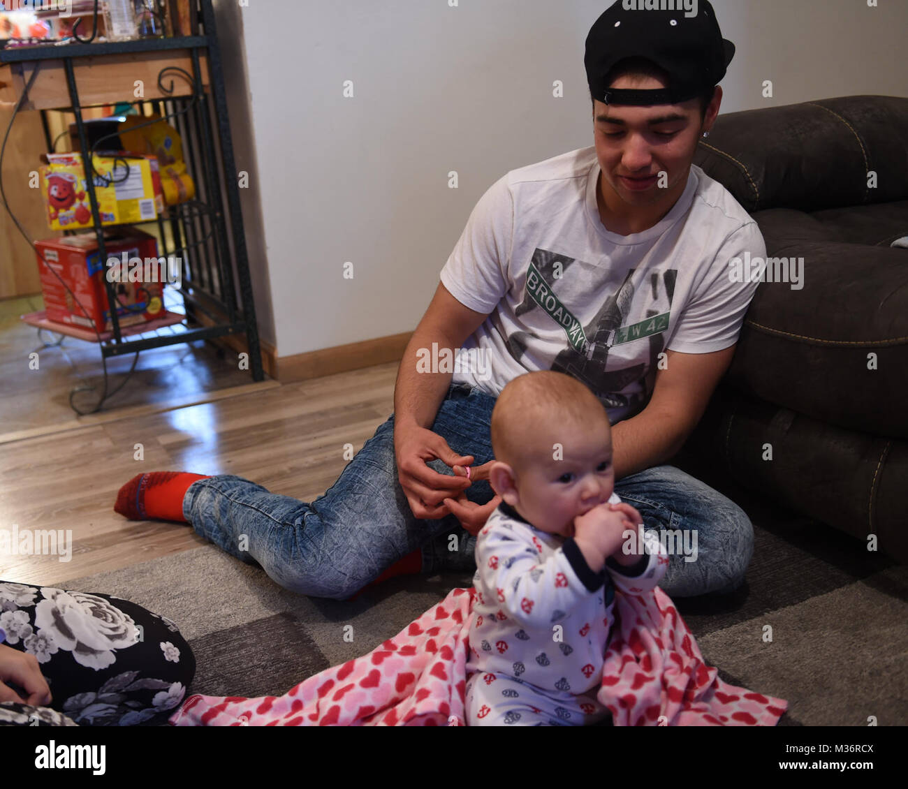 Tyger Rodriguez, 17, of Torrington, Wyoming, smiles at his six-month-old son Kyson, during his home visit from Wyoming - Stock Image
