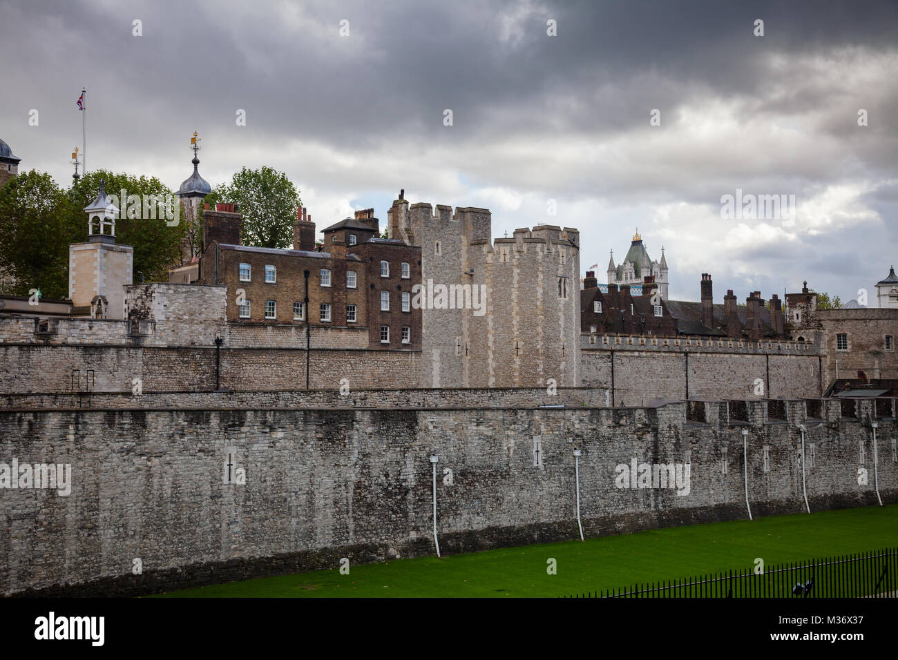 The outer curtain wall and dry moat of Tower of London - historic castle and popular tourist attraction on the north Stock Photo