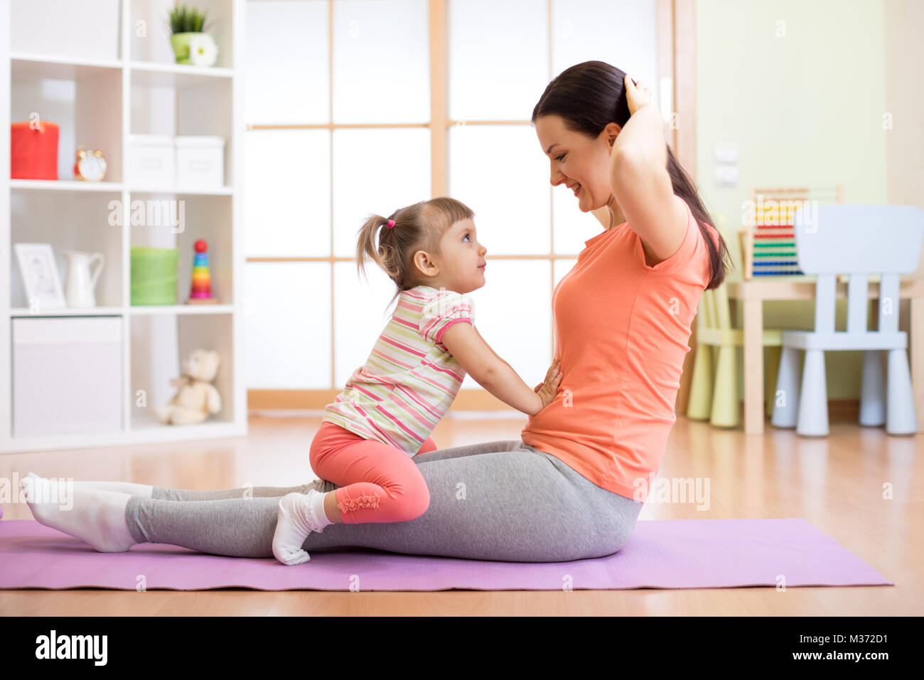 Mom and child doing fitness exercises on mat at home Stock