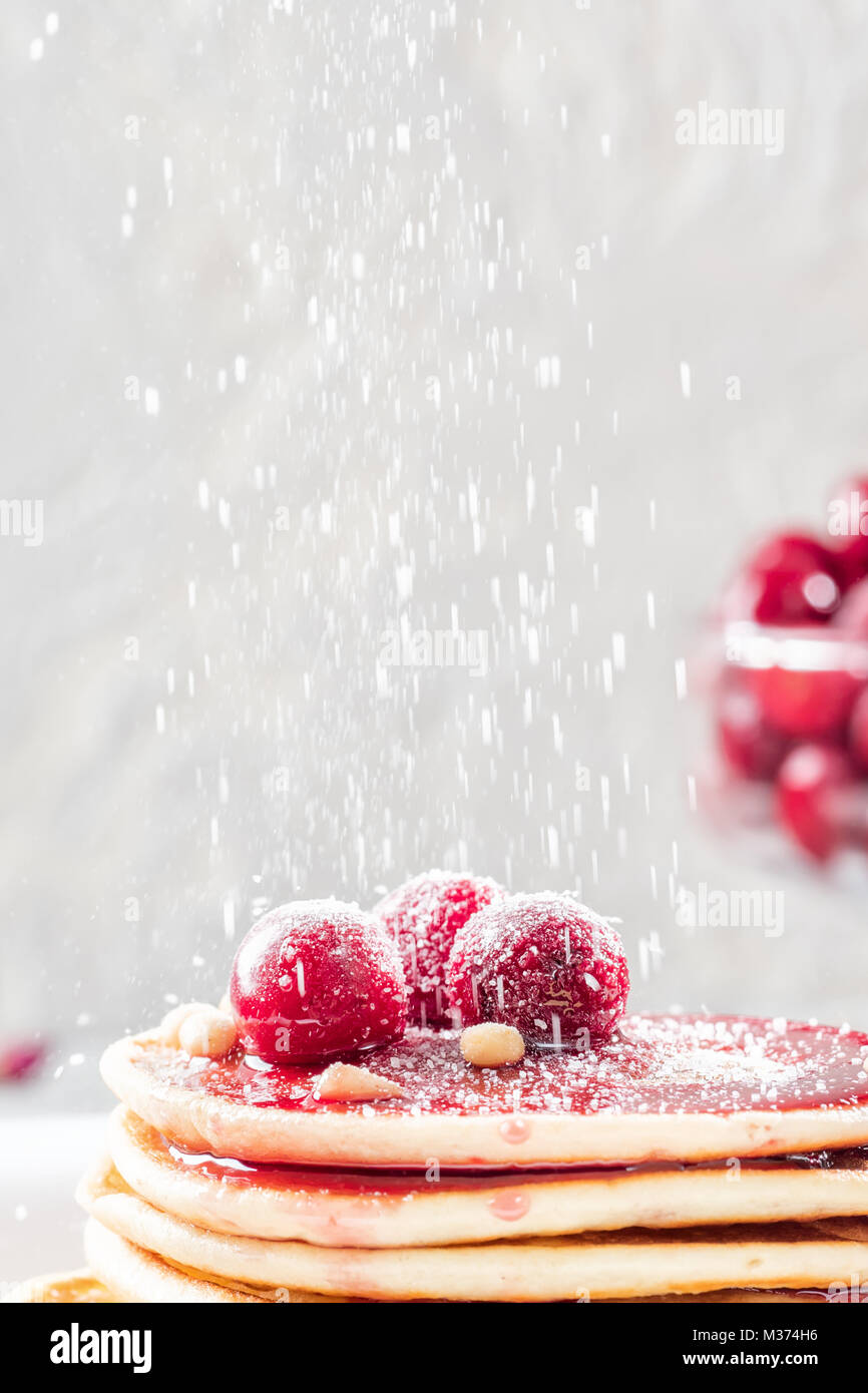 Pancakes homemade cake in stack decorated with berries frozen cherry Sprinkle with sugar powder on white plate - Stock Image