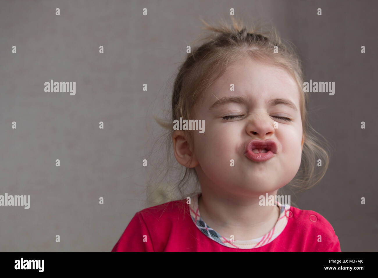 Clouse-up portrait of cheerful little girl gesturing and making funny grimace at camera. Have you smiled today - Stock Image