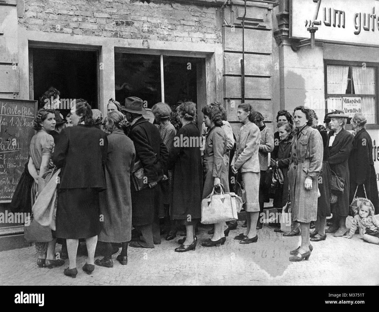 Because of food shortages in the post-war era, people are standing in a line in front of a store.   usage worldwide - Stock Image