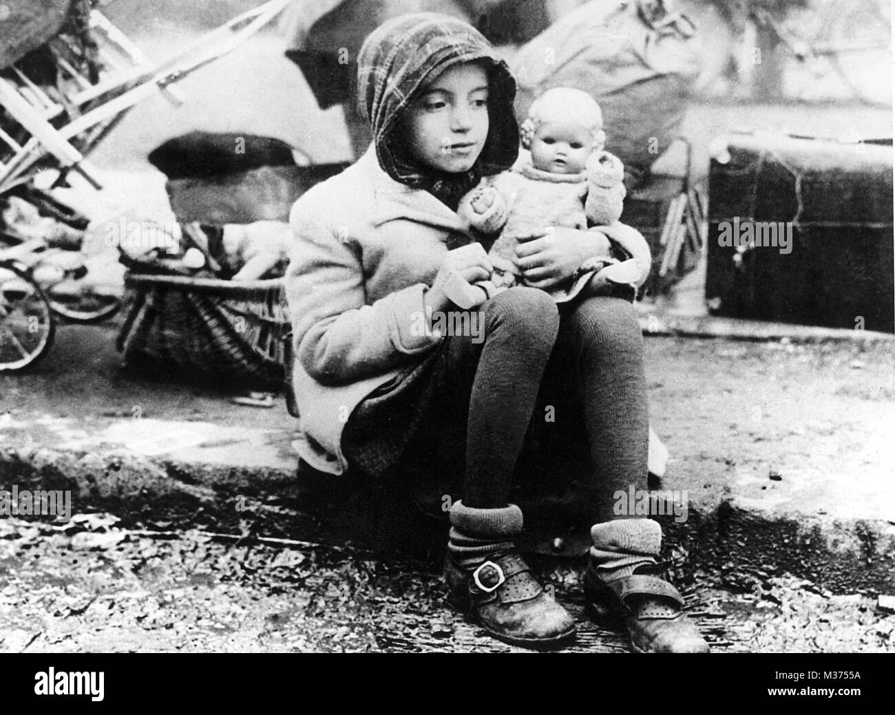 A girl from a refugee trek, with her doll in her arms, in the turmoil of the post-war era.   usage worldwide - Stock Image