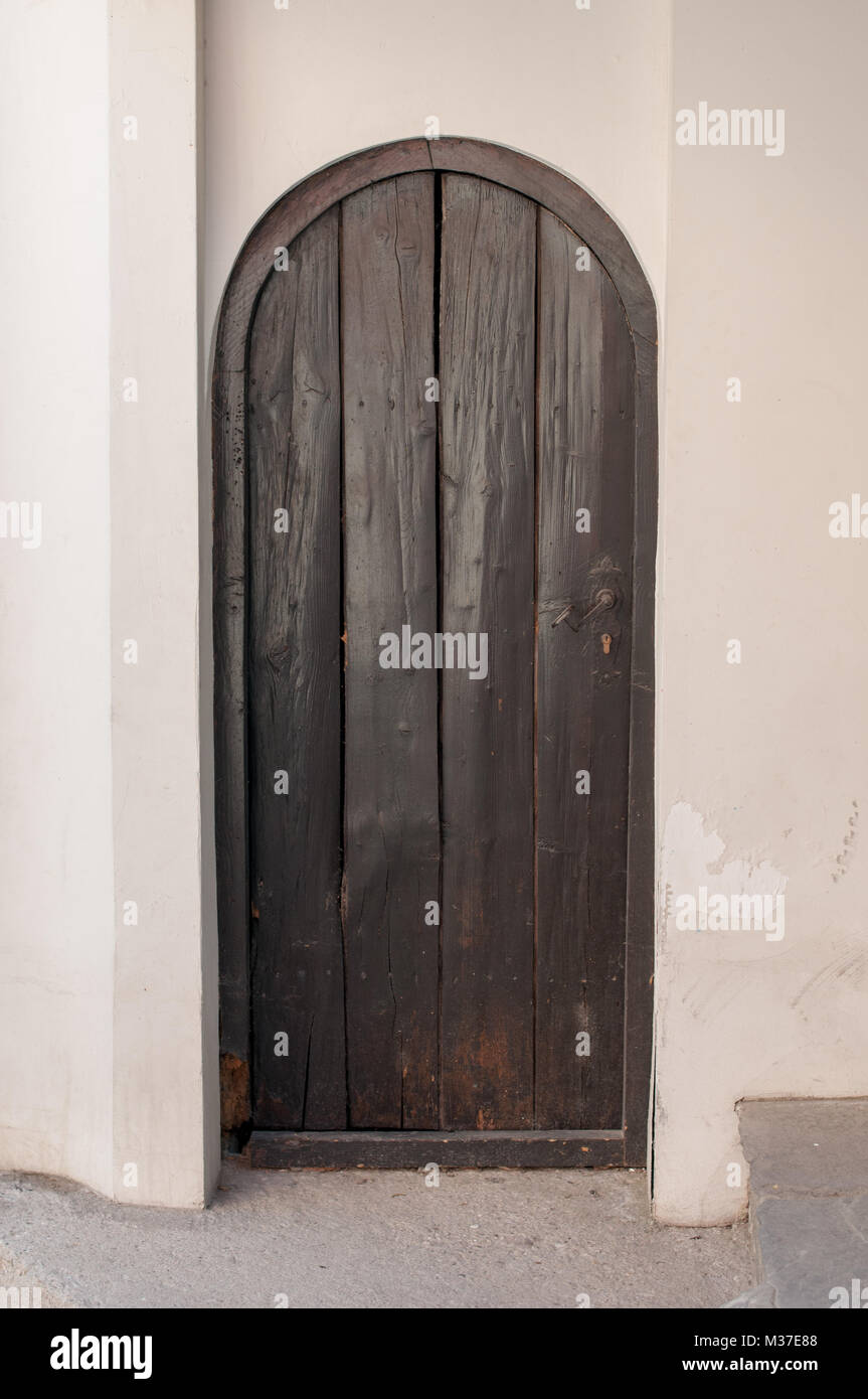 Old wooden door with rusty lock  in white wall Stock Photo