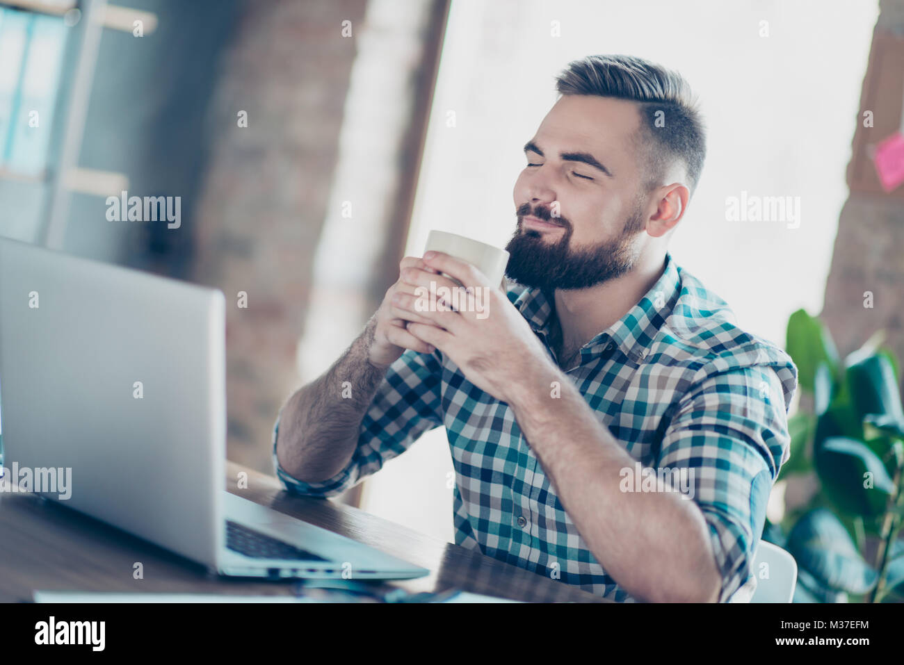 It will be easy for me! Smiling cunning happy cheerful manager wearing checkered shirt is enjoying a cup of fresh - Stock Image