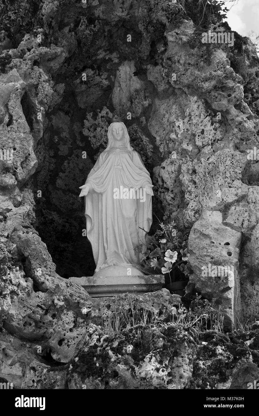 Statue of Our Lady of Lourdes in the Grotto in the grounds of Château de Sully in the Loire Valley, France - Stock Image
