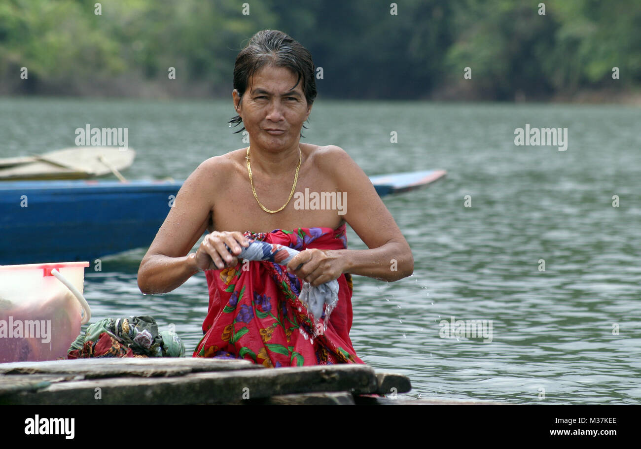 A local resident washes clothing in the Batang Ai National Park reservoir,  in Sarawak, Borneo, August 3, 2005 - Stock Image