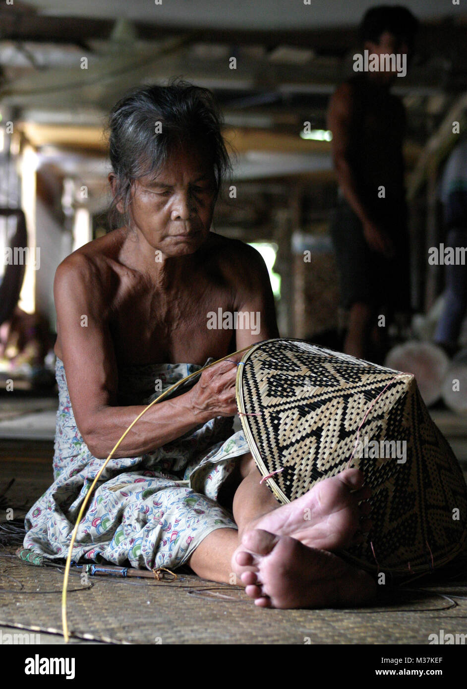A local resident weaves a hat in a longhouse set in rainforest in the Batang Ai National Park, in Sarawak, Malaysia - Stock Image