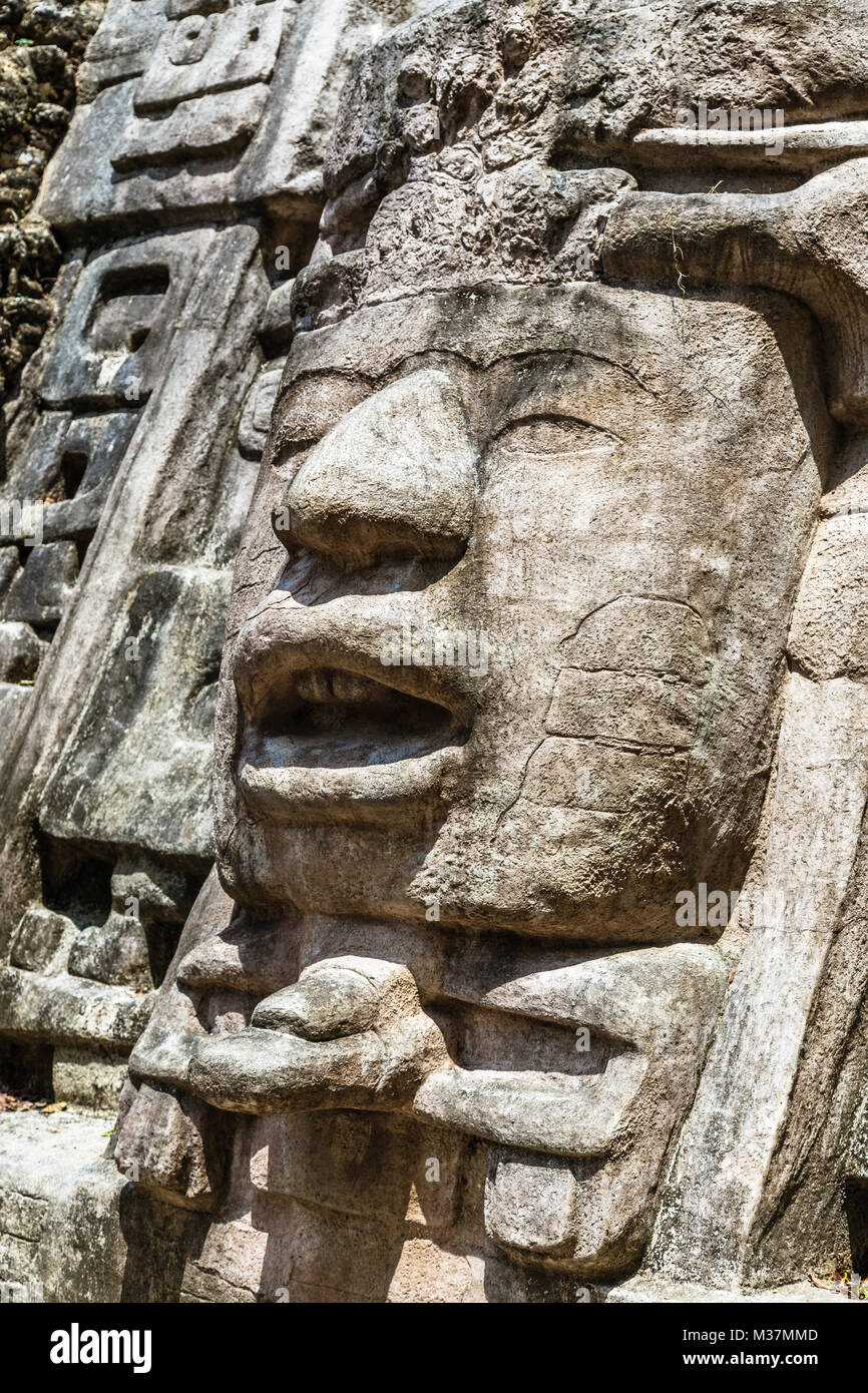 Old ancient stone Mayan pre-columbian civilization carved face and ornament, Lamanai archeological site, Orange - Stock Image