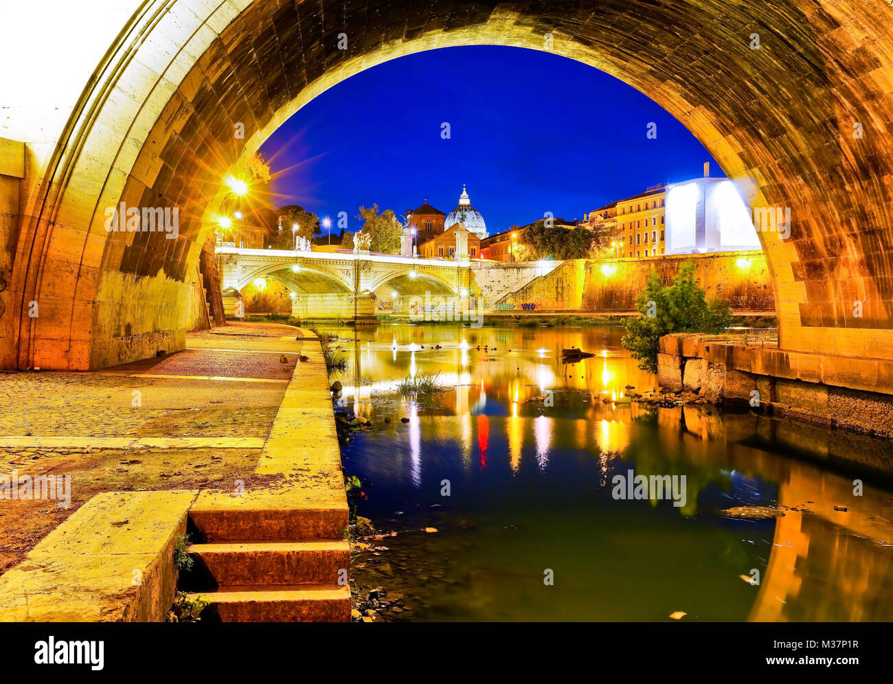 View of St. Peter's Basilica from Aelian Bridge in Rome at night. - Stock Image
