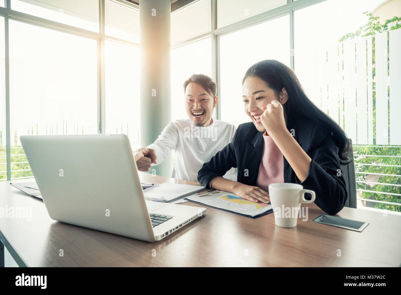 Asian couple business people with casual suit working with happy action in office Business people concept. - Stock Image