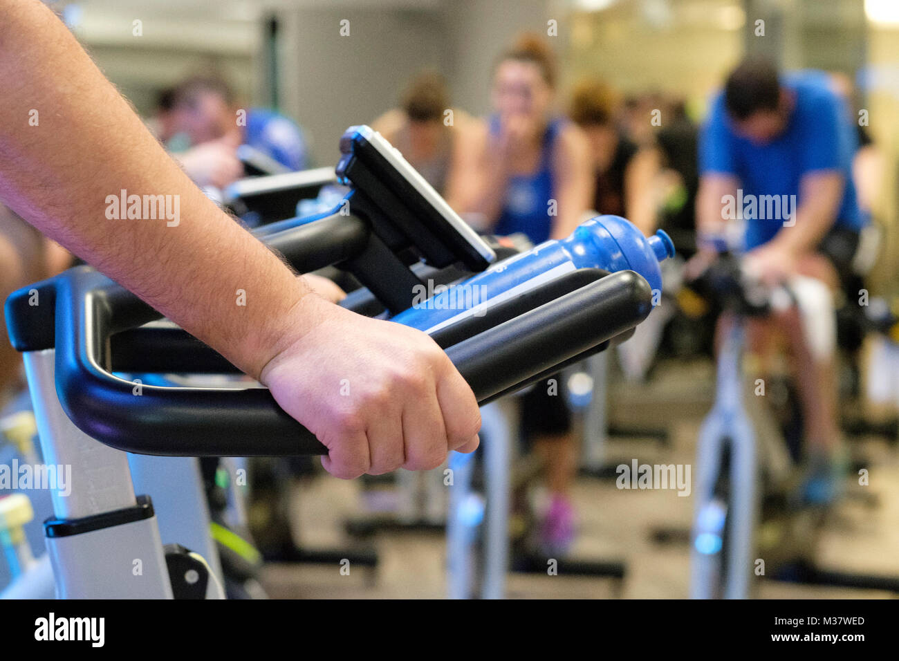 Close up of person during a spinning class at the gym - Stock Image