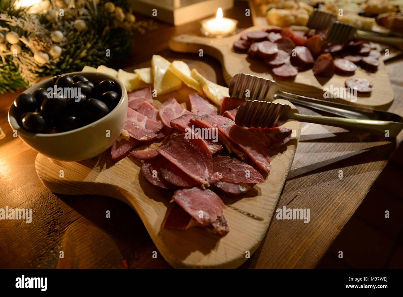 Food buffet with olives, cheese, ham and chourizo platters - Stock Image