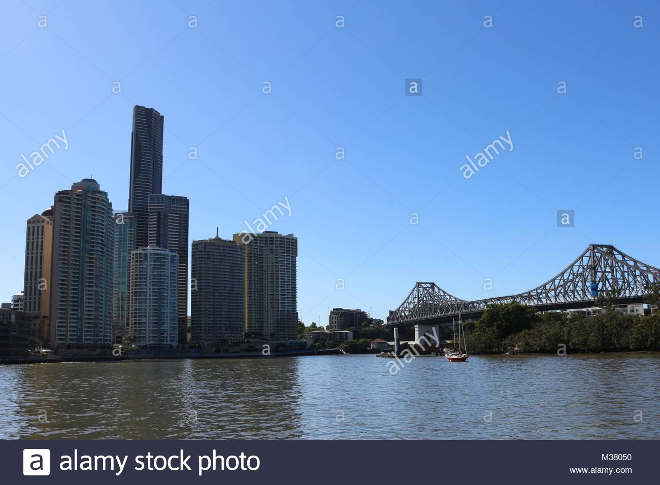 Story bridge and skyscrapers under blue skies in Brisbane, Australia - Stock Image