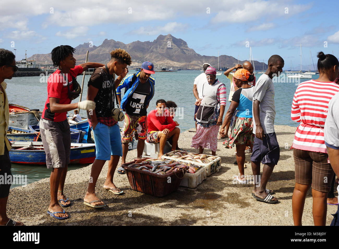 People on the landing Stage of the fish market in Mindelo, watching the unloading of fishes Stock Photo