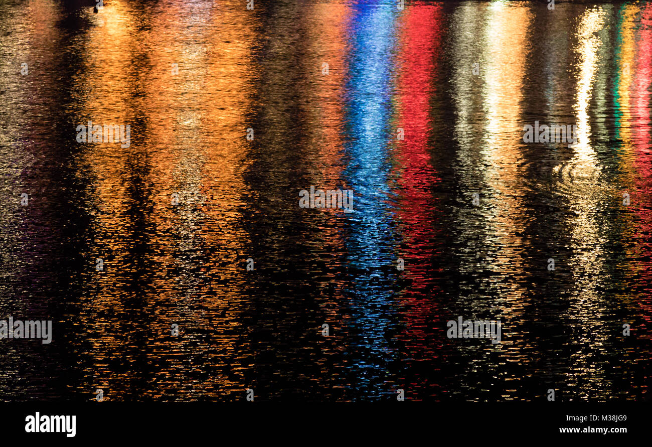 Multicoloured lights reflected in the water of the harbour in Porthleven Cornwall at night. - Stock Image