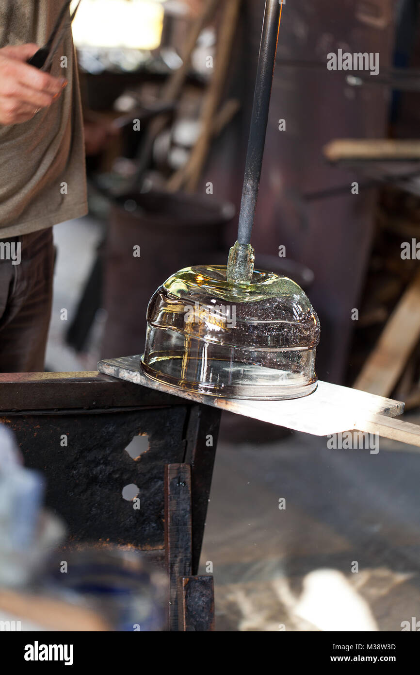 glass blower carefully making his product - Stock Image