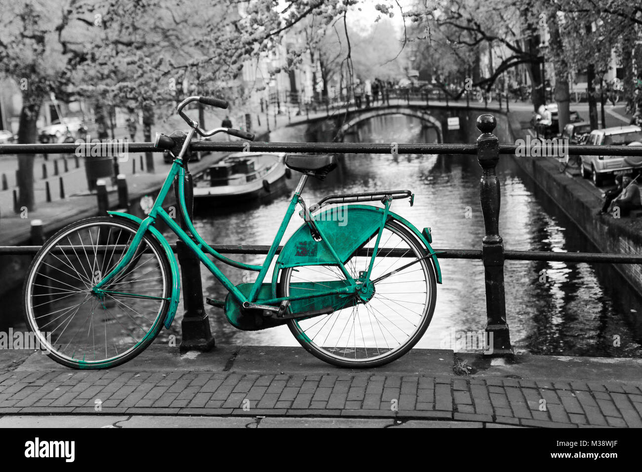 A picture of a lonely azure bike on the bridge over the channel in Amsterdam. The background is black and white. Stock Photo