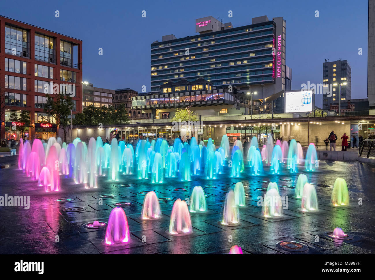 Coloured Fountain at night, Piccadilly Gardens, Manchester, Greater Manchester, England, UK - Stock Image