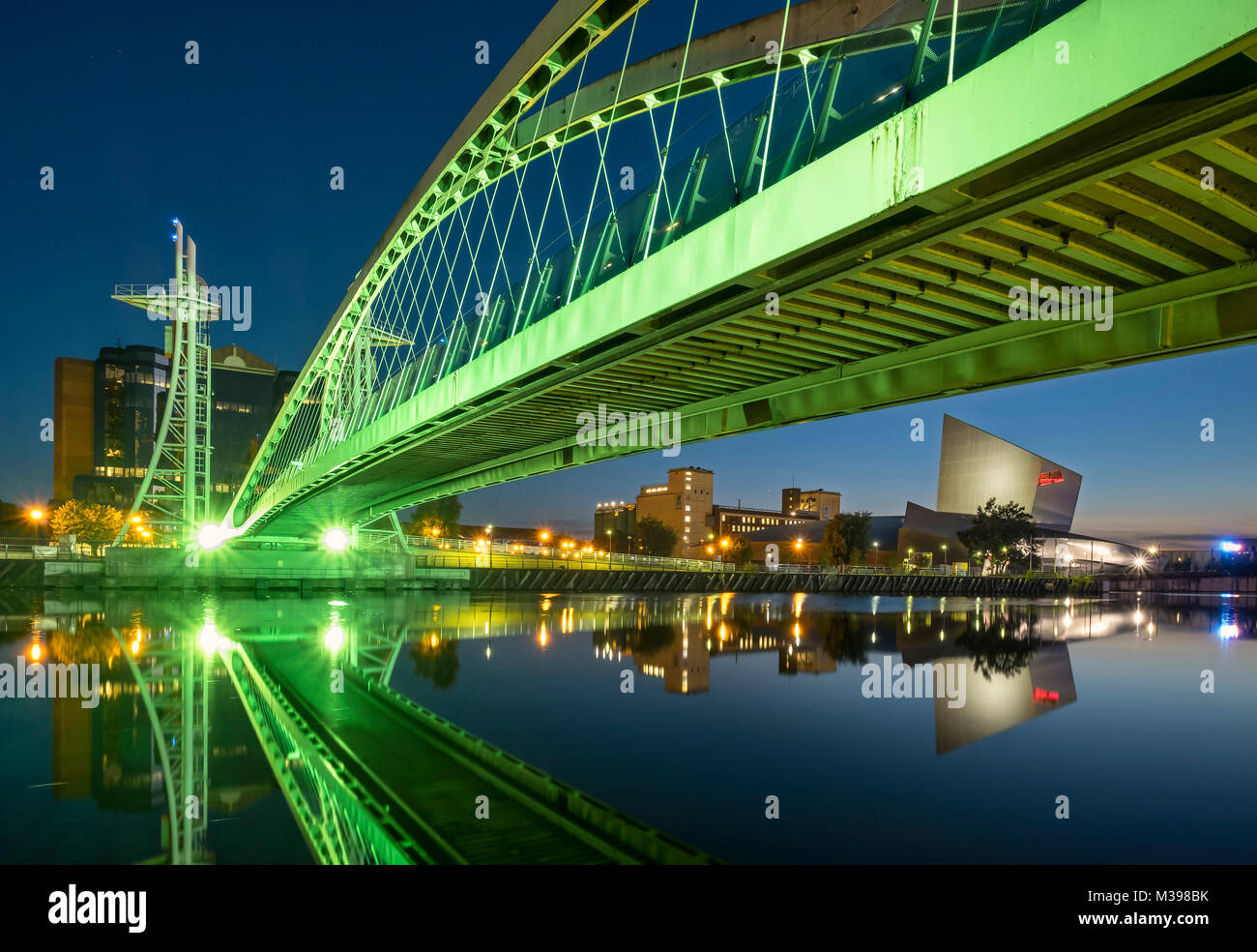 Lowry Footbridge and Imperial War Museum North at night, Salford Quays, Greater Manchester, England, UK - Stock Image