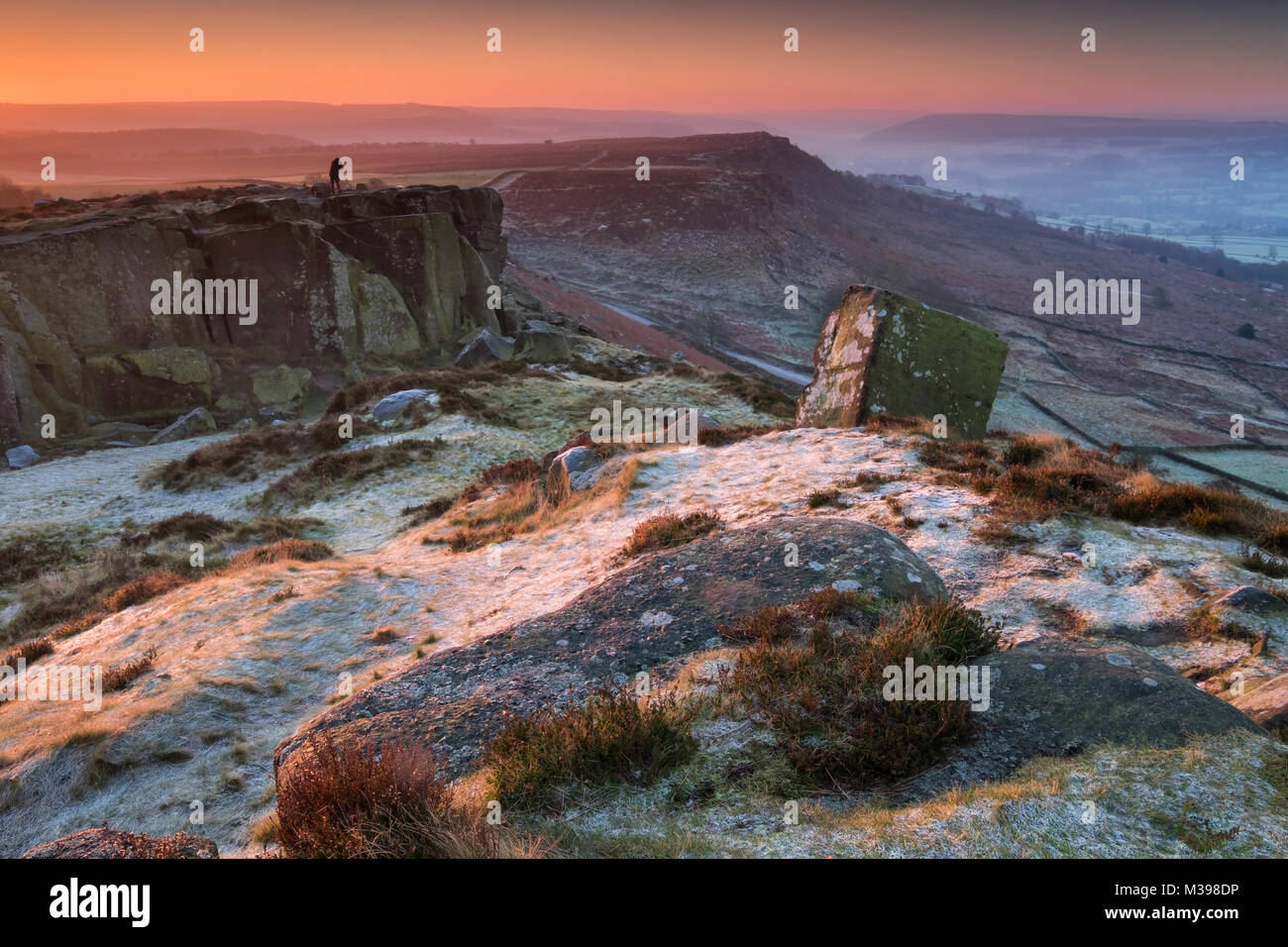 A photographer stands at dawn on frost covered Curbar Edge in winter, near Calver, Peak District National Park, - Stock Image