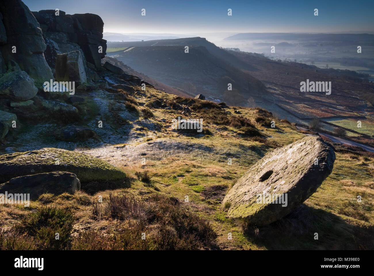 Abandoned Millstone on Curbar Edge in winter, Peak District National Park, Derbyshire, England, UK - Stock Image