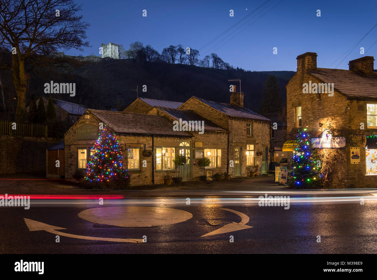 Shops in Castleton at Christmas backed by Peveril Castle at night, Peak District National Park, Derbyshire, England, - Stock Image