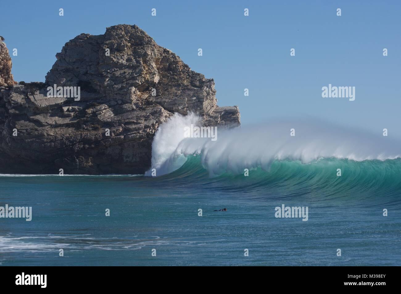 Wave breaking at Praia do Barranco, Algarve, Portugal - Stock Image