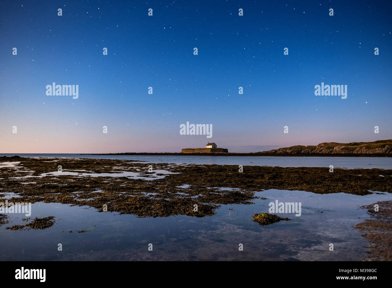 The night sky over St Cwyfan's Church, Aberffraw, Anglesey, North Wales, UK - Stock Image