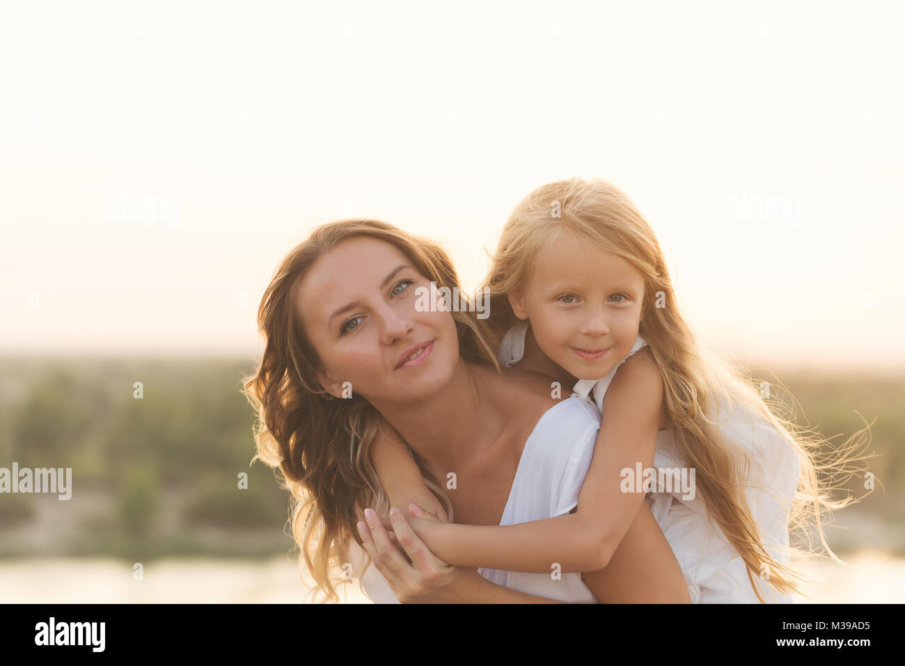 Family, mother and daughter. Girl Piggyback Daughter. Girls in white dresses. They are blondes. Family time together. - Stock Image