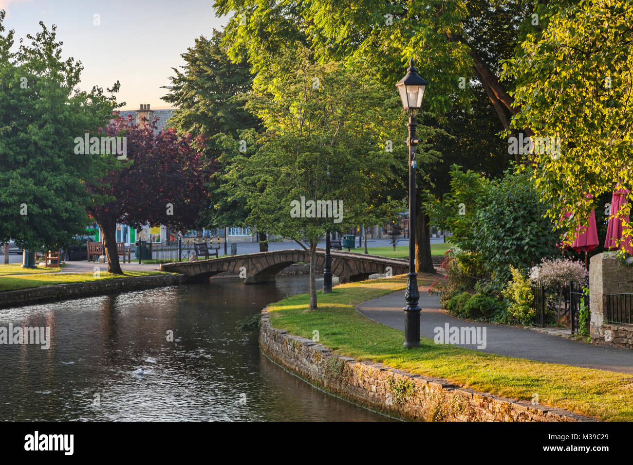 The River Windrush flows under the famous stone bridge in the Cotswolds village of Bourton-on-the-Water, Gloucestershire, - Stock Image