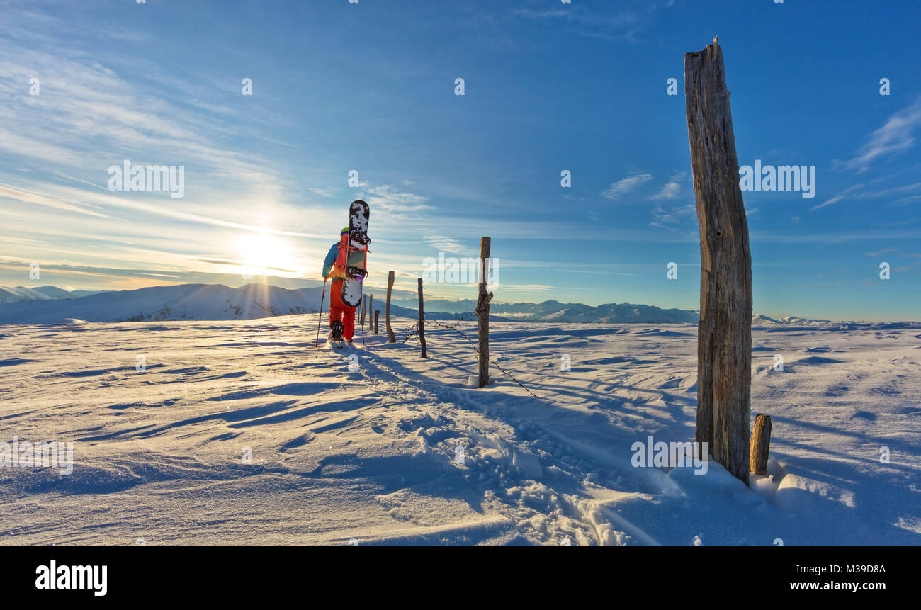 Backview of snowboarder walking on snowshoes in powder snow. European Alpine scenery, winter sports and activities - Stock Image