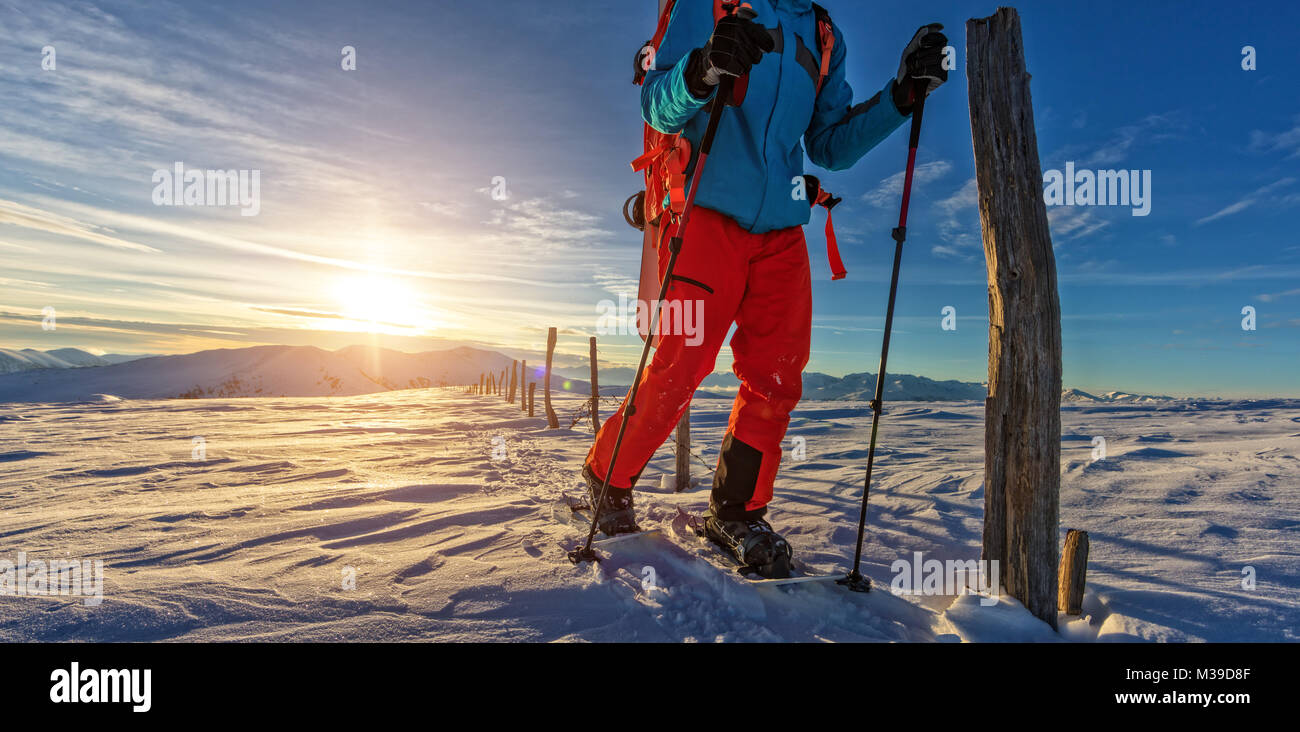 Closeup of snowboarder walking on snowshoes in powder snow. European Alpine scenery, winter sports and activities - Stock Image