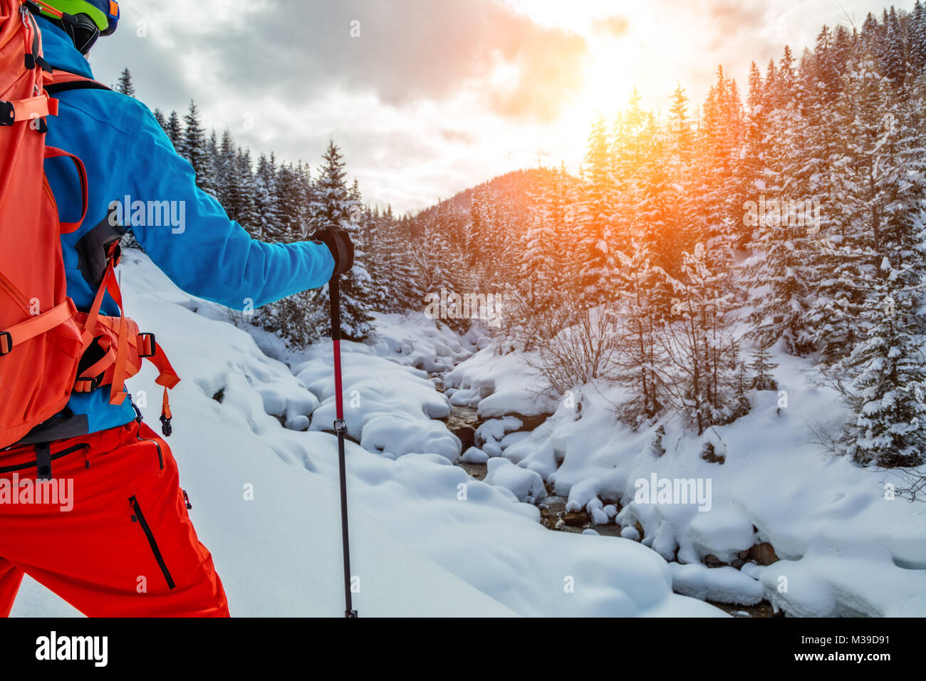 CLoseup of young man walking on snowshoes in powder snow. European Alpine scenery, winter sports and activities - Stock Image