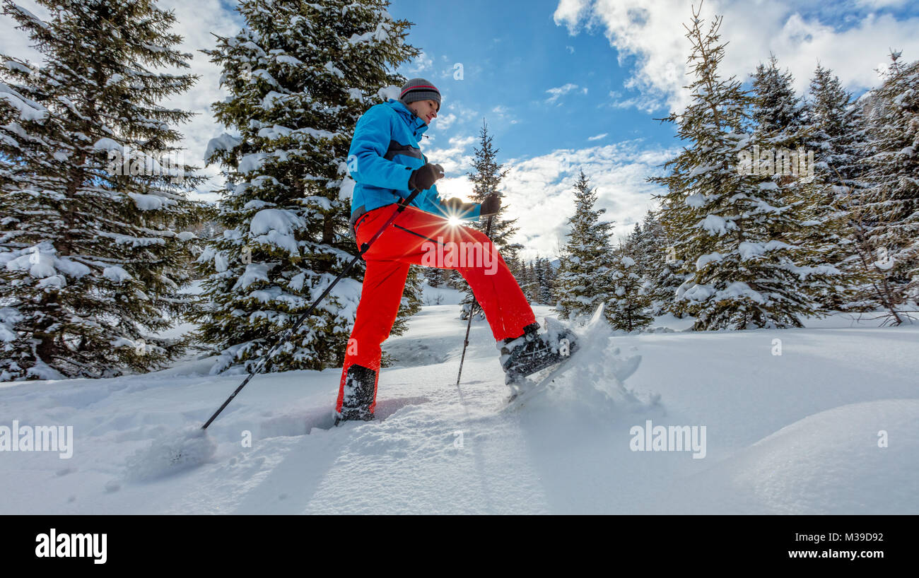 Young man walking on snowshoes in powder snow. European Alpine scenery, winter sports and activities - Stock Image