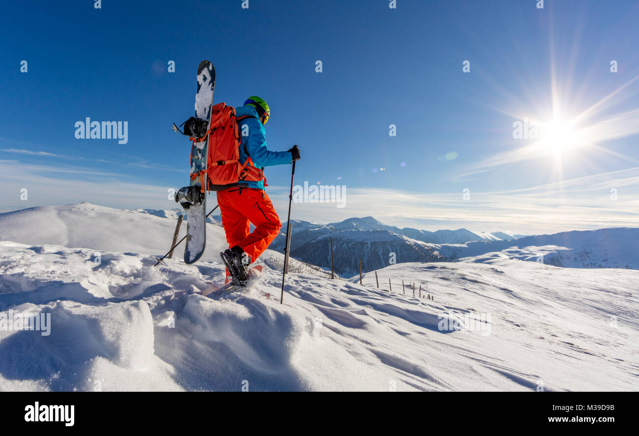 Snowboarder walking on snowshoes in powder snow. European Alpine scenery, winter sports and activities - Stock Image