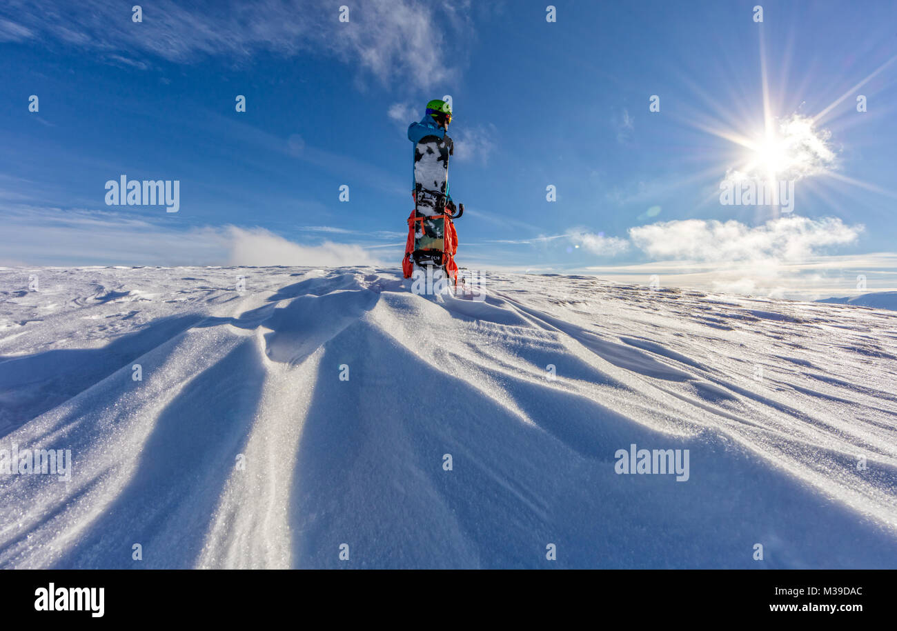 Snowboarder on the top of mountain, ready to downhill run off piste. European Alpine scenery in sunset light - Stock Image