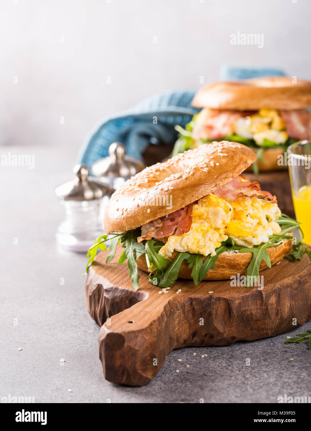 Bagels with scrambled eggs, rucola and fried bacon - Stock Image