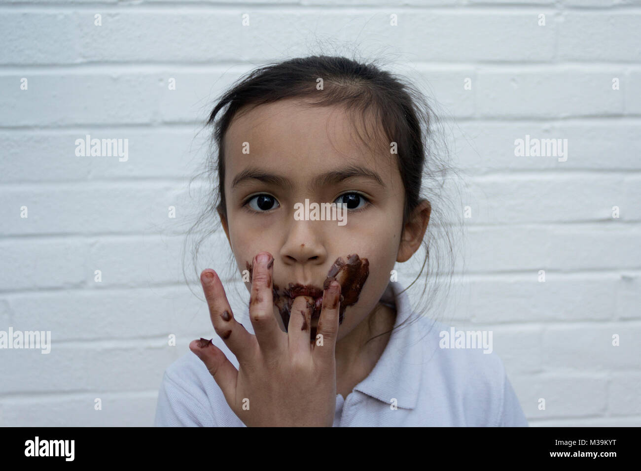 child eating chocolate with mess on face - Stock Image
