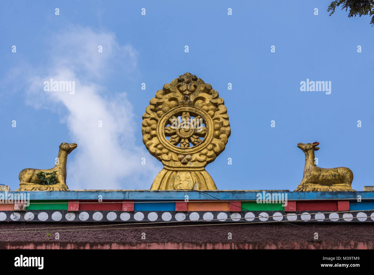 Coorg, India - October 29, 2013: Chakra and deer statues on top of monk and nun quarters at Namdroling Buddhist - Stock Image