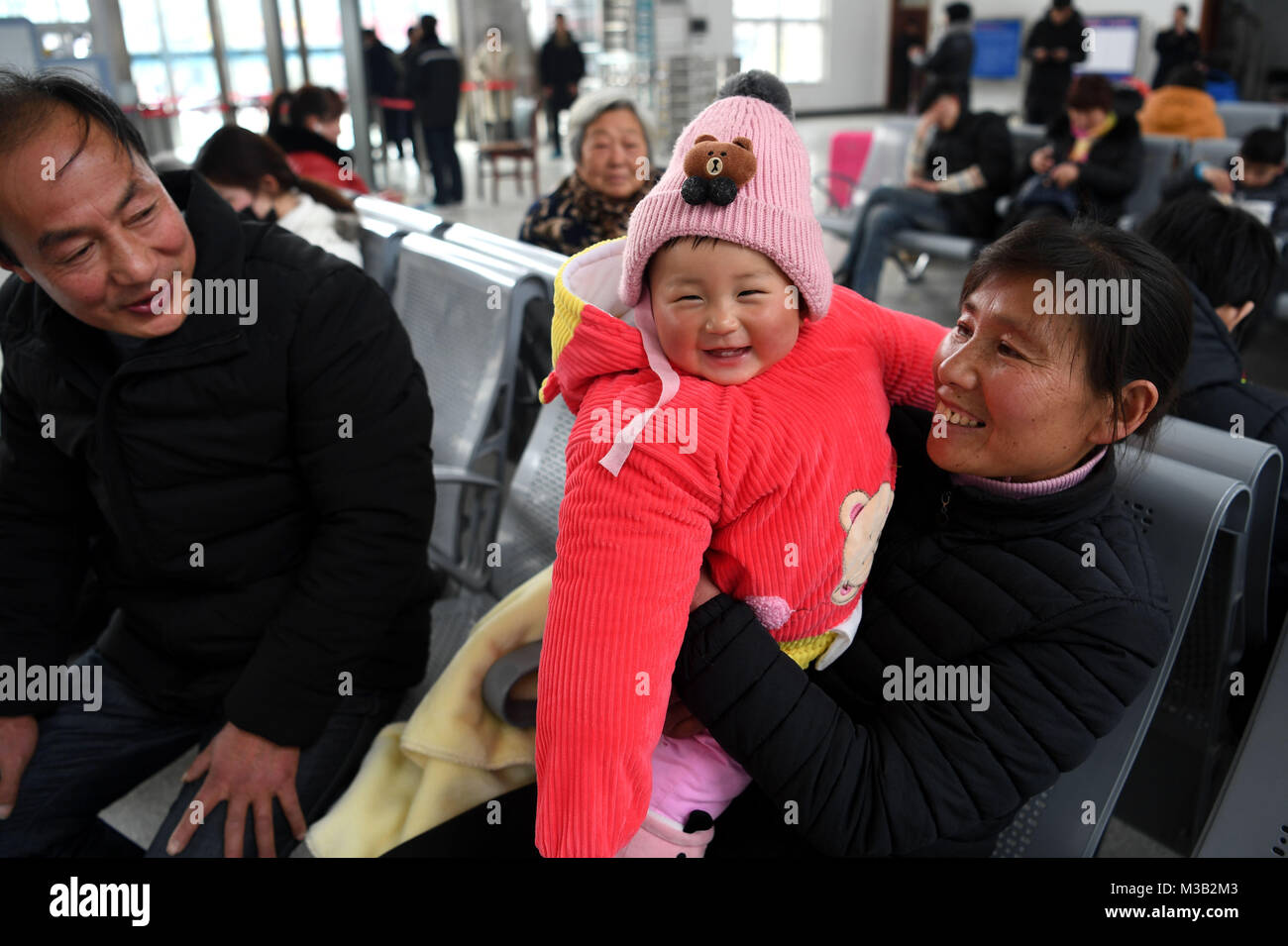 Yingshang. 10th Feb, 2018. Nine-month-old Chang Liuyi are held by her grandparents to take a train to Changzhou - Stock Image